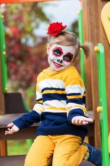 Una bambina in età prescolare con la faccia dipinta, ha scalato lo scivolo nel parco giochi, celebra halloween o il giorno dei morti messicano.
