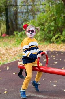 Una bambina in età prescolare con la faccia dipinta, cavalca su un'altalena nel parco giochi, celebra halloween o il giorno dei morti messicano.
