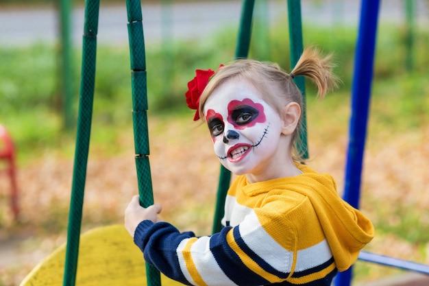 Una bambina in età prescolare con la faccia dipinta, mostra facce buffe nel parco giochi, celebra halloween o il giorno dei morti messicano.