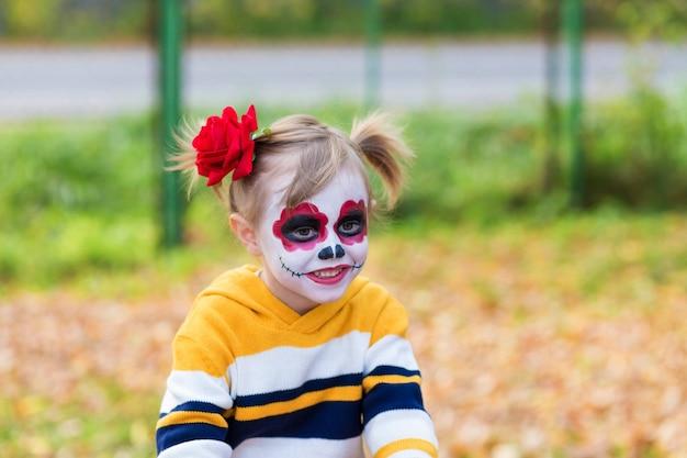 Una bambina in età prescolare con la faccia dipinta, sorridente nel parco giochi, celebra halloween o il giorno dei morti messicano.