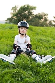 Piccola bella ragazza sui pattini a rotelle in casco all'aperto in una bella giornata estiva