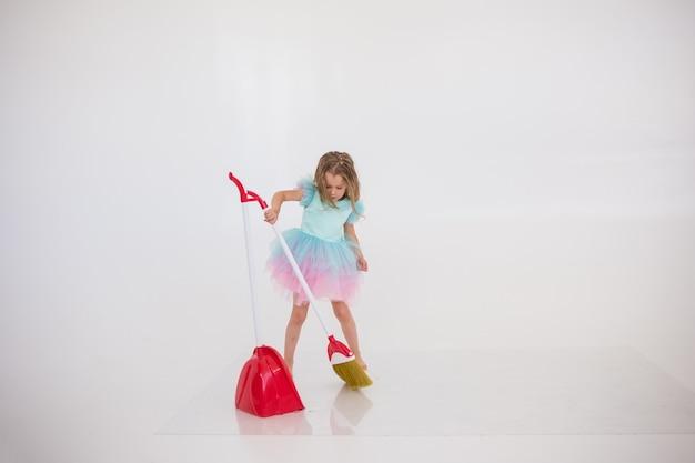 Una piccola principessa in abito festivo fa le pulizie su uno sfondo bianco con un posto per il testo