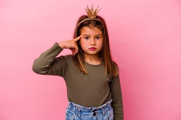 Piccola principessa ragazza con corona isolato sul muro rosa che punta tempio con il dito, pensando, concentrato su un compito