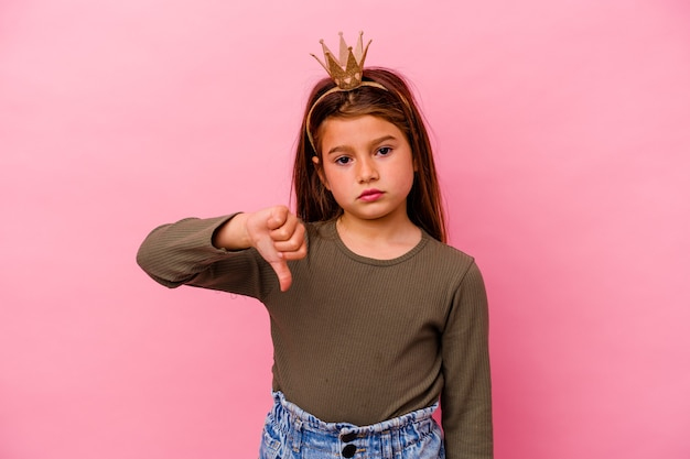 Piccola ragazza principessa con corona isolata sulla parete rosa che mostra un gesto di avversione, pollice in giù concetto di disaccordo