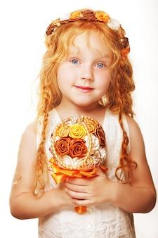 Piccola principessa in posa con bouquet di rose artificiali