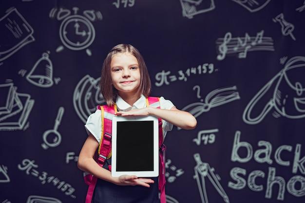 Piccolo allievo che si prepara ad andare a scuola con lo zaino che mostra il concetto di tablet torna a scuola