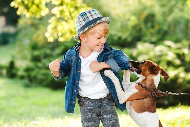 Piccolo cucciolo jack russel terrier morde il suo proprietario durante la passeggiata. ragazzo e cane migliori amici. bambino con cane che cammina nel parco estivo. bambino felice che si diverte insieme al cane all'aperto.