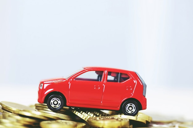 Piccola automobile rossa sopra molte monete impilate dei soldi. per prestiti bancari costi di finanziamento. assicurazione, acquisto del concetto di finanziamento auto. acquistare e pagare a rate l'acconto di un'auto.