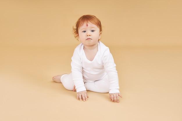 La piccola neonata dai capelli rossi sta giocando su un fondo beige. un grosso neo sulla fronte, non come tutti gli altri