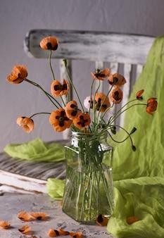 Un po' di bouquet di papaveri rossi disposti in stile classico stillife di papaveri in un vaso di bicchieri su vintage cher