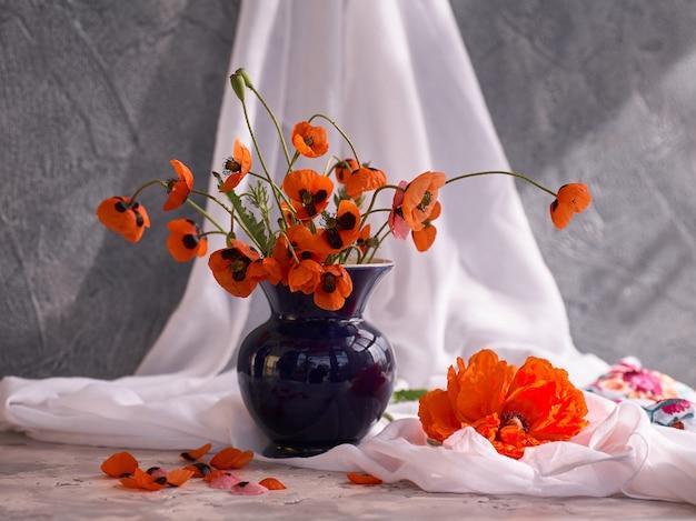 Un piccolo bouquet di papaveri rossi in vaso di ceramica blu