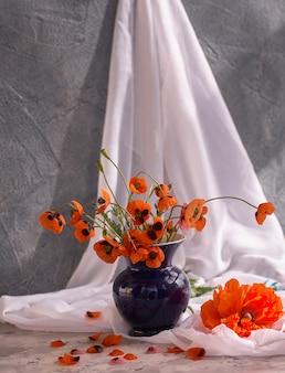 Un piccolo mazzo di papaveri rossi in vaso di ceramica blu
