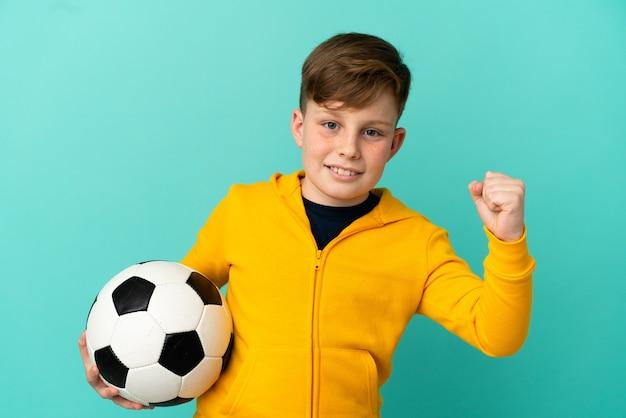 Ragazzino dai capelli rossi isolato su sfondo blu con pallone da calcio che celebra una vittoria