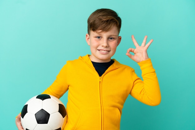 Ragazzino dai capelli rossi isolato su sfondo blu con pallone da calcio e facendo segno ok