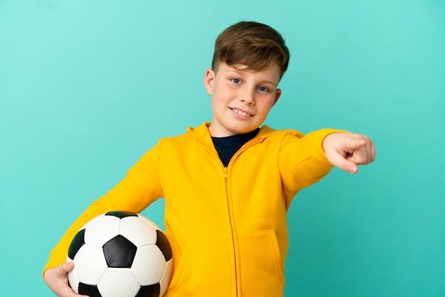 Ragazzino dai capelli rossi isolato su sfondo blu con pallone da calcio e rivolto verso la parte anteriore
