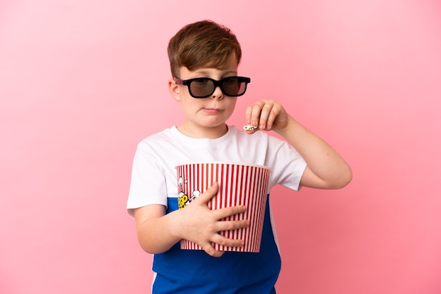 Ragazzino dai capelli rossi isolato su sfondo rosa con occhiali 3d e con in mano un grosso secchio di popcorn