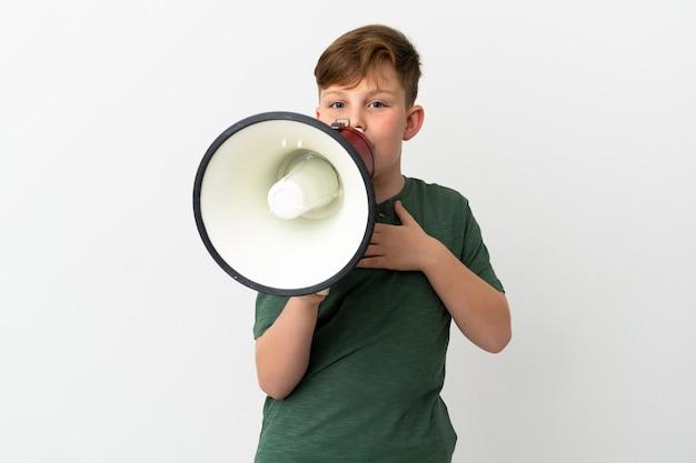Ragazzino dai capelli rossi isolato su sfondo bianco che grida attraverso un megafono con espressione sorpresa