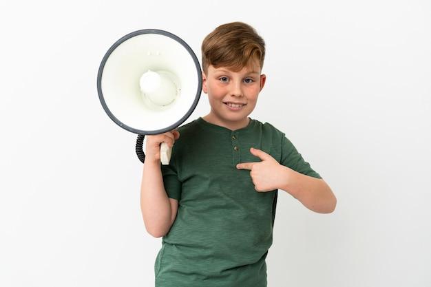 Ragazzino dai capelli rossi isolato sul muro bianco con in mano un megafono e con espressione facciale a sorpresa
