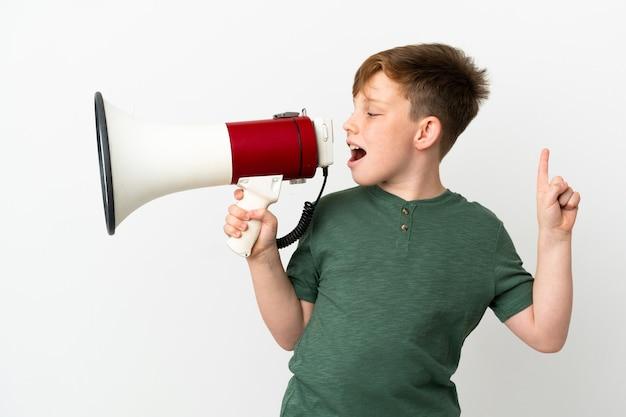 Ragazzino dai capelli rossi isolato sul muro bianco che grida attraverso un megafono per annunciare qualcosa in posizione laterale