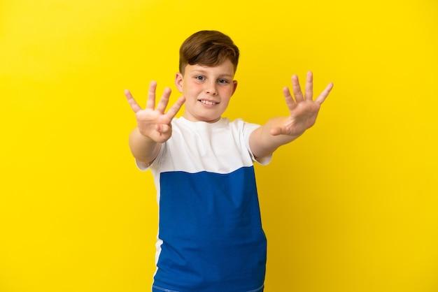 Ragazzino dai capelli rossi isolato su sfondo giallo che conta nove con le dita