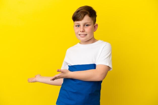 Ragazzino dai capelli rossi isolato su sfondo giallo che allunga le mani di lato per invitare a venire