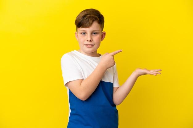 Ragazzino dai capelli rossi isolato su sfondo giallo che tiene un copyspace immaginario sul palmo per inserire un annuncio