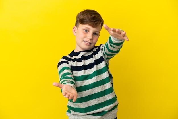 Ragazzino dai capelli rossi isolato su sfondo giallo che presenta e invita a venire con la mano