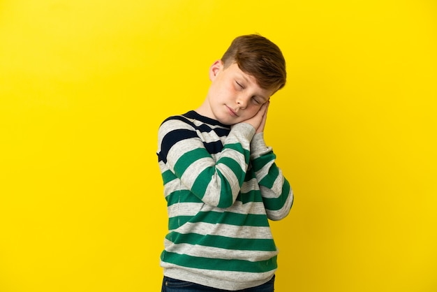Ragazzino dai capelli rossi isolato sulla superficie gialla che fa il gesto del sonno in un'espressione adorabile