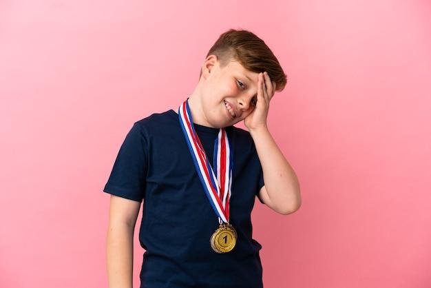 Il ragazzino dai capelli rossi con medaglie isolate su sfondo rosa ha realizzato qualcosa e intendeva la soluzione