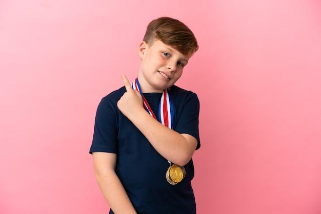 Ragazzino dai capelli rossi con medaglie isolate su sfondo rosa che puntano al lato per presentare un prodotto