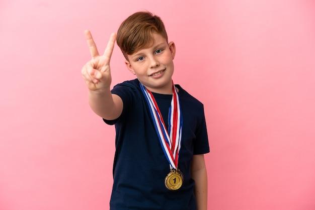 Ragazzino dai capelli rossi con medaglie isolate su sfondo rosa che sorride e mostra il segno della vittoria