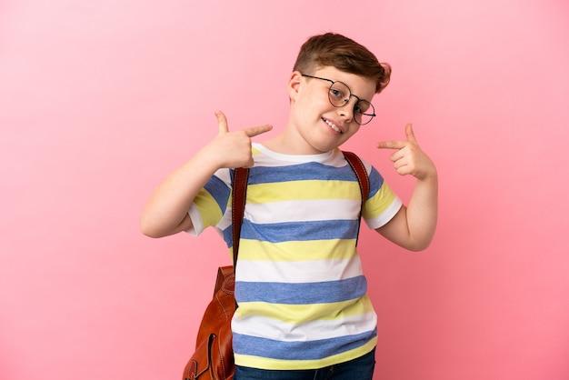 Piccolo ragazzo caucasico dai capelli rossi isolato su sfondo rosa che dà un gesto di pollice in alto
