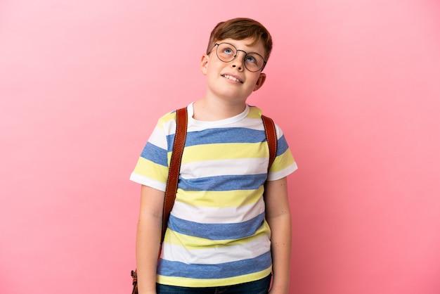 Piccolo ragazzo caucasico dai capelli rossi isolato su sfondo rosa pensando a un'idea mentre guarda in alto