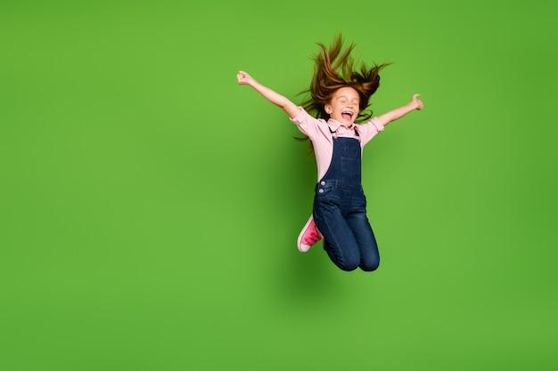 Piccola ragazza della testarossa che posa contro il muro verde