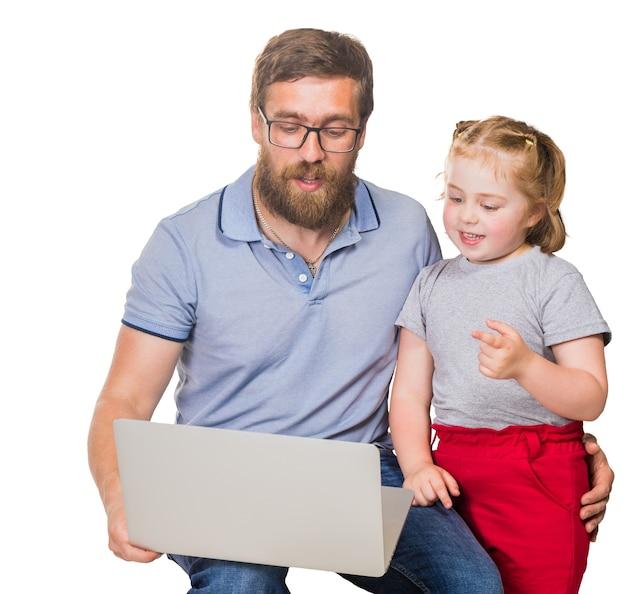 Piccola ragazza dai capelli rossi con papà dietro un computer portatile su uno sfondo bianco isolato