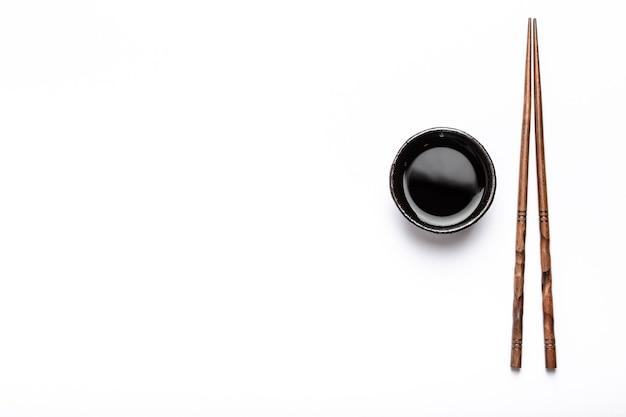 Piccola ciotola rustica con salsa di soia e bacchette di legno su sfondo bianco con spazio per il testo. concetto di ristorante di sushi, cucina giapponese o modello di menu, vista dall'alto
