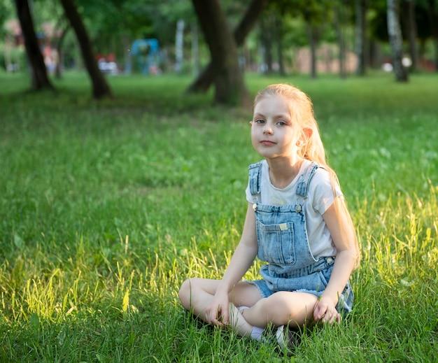 Bambina triste seduta nel parco sull'erba