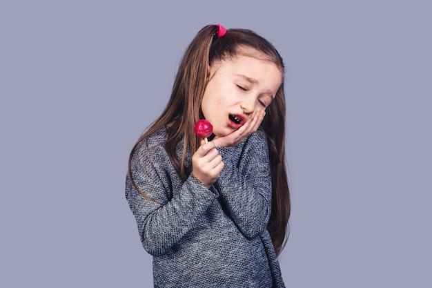 Piccola ragazza triste con un lecca-lecca rosso tra le mani, i cui denti fanno male. il concetto di sviluppo della carie dovuto all'abuso di caramelle. isolato su superficie grigia