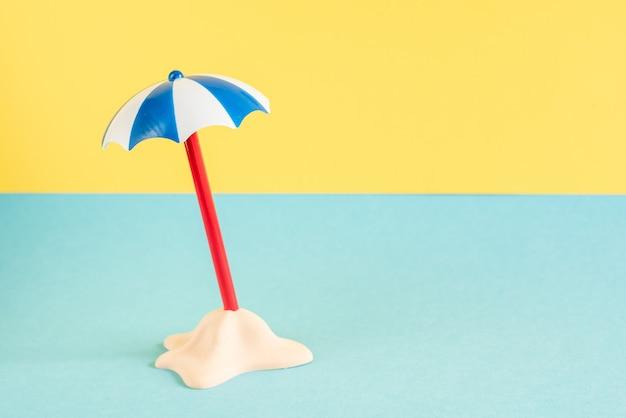 Poca isola di sabbia con ombrello su sfondo blu pastello