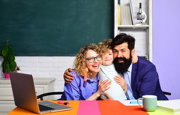 Il ragazzino della scuola elementare di prima elementare collabora con i genitori che incoraggiano la loro