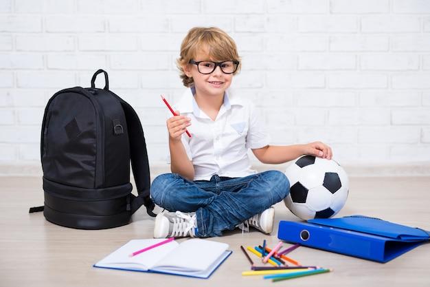 Piccolo scolaretto con gli occhiali che fa i compiti a casa
