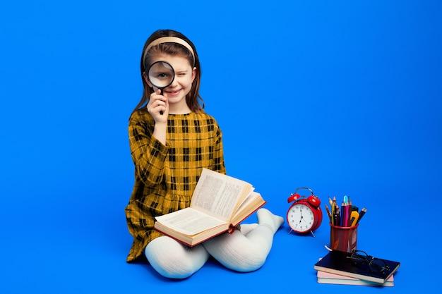 Piccola scolara in abito a scacchi con lente d'ingrandimento e sorridente