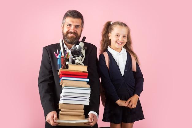 La piccola scolaretta e l'insegnante di piume con in mano un libro con la borsa della scuola sono tornati a scuola, spazio vuoto in studio, isolato su sfondo colorato. concetto educativo per la scuola.