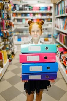 La bambina della scuola tiene cartelle colorate in cartoleria