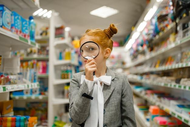 La ragazzina della scuola guarda attraverso la lente d'ingrandimento, facendo shopping nel negozio di cancelleria