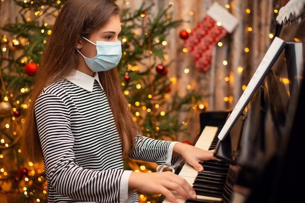 Piccola ragazza della scuola che suona il pianoforte nella mascherina medica protettiva per prevenire la malattia di covid