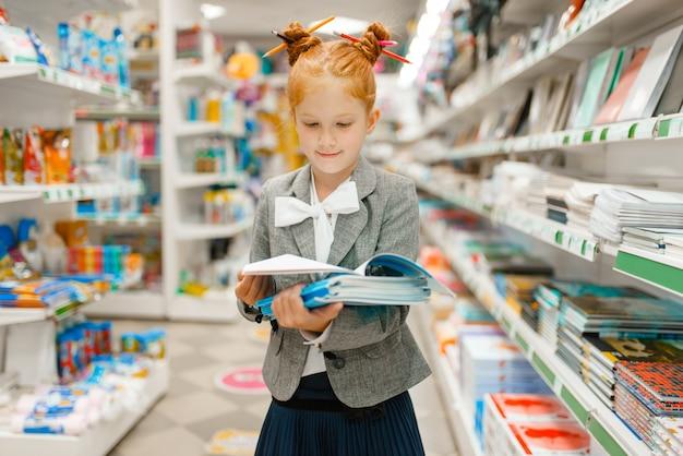 Bambina della scuola con i taccuini in cartoleria. bambina che compra forniture per ufficio in negozio, scolaretta al supermercato