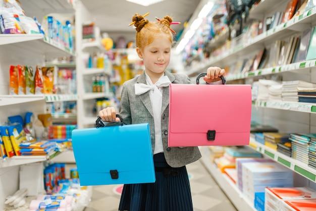 Bambina della scuola con due cartelle in cartoleria. bambina che compra forniture per ufficio in negozio, scolaretta al supermercato