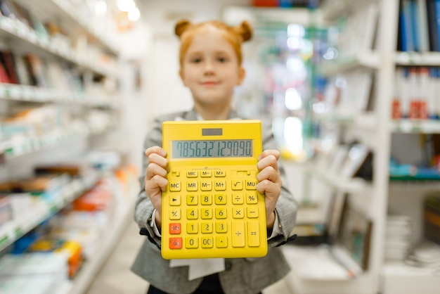 Piccola scolaretta con calcolatrice gialla, shopping in cartoleria