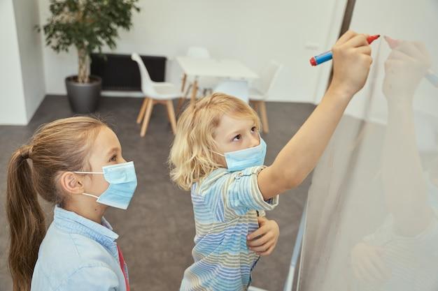 Ragazzini della scuola, ragazzo e ragazza che indossano una maschera protettiva durante la pandemia di coronavirus, ragazzo che scrive su